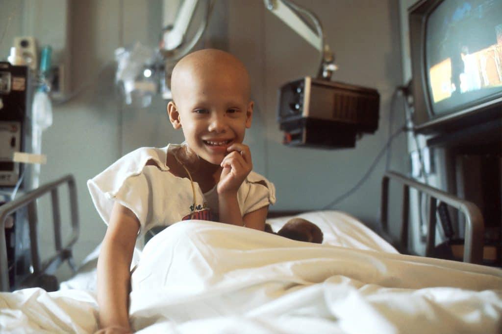Criança vítima de câncer em uma maca de hospital, sorrindo.