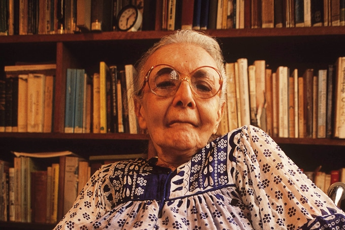Fotografia de Nise da Silveira (1905-1999) em frente a uma estante de livros.
