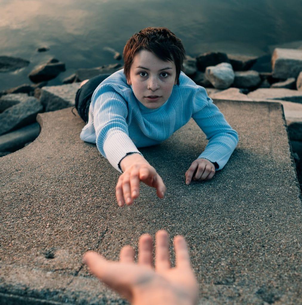Mulher com a mão estendida caindo no mar
