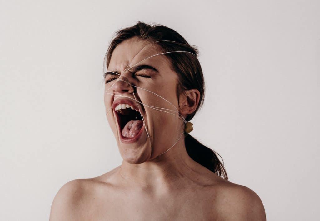 Mulher com linhas apertando seu rosto gritando