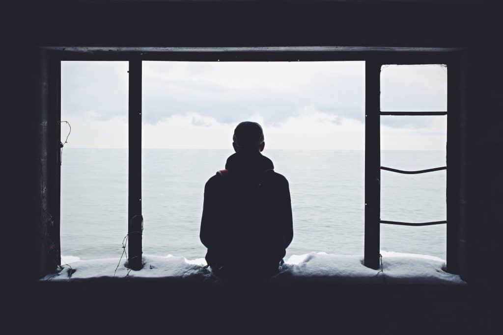 Pessoa sozinha sentada na janela e observando o horizonte
