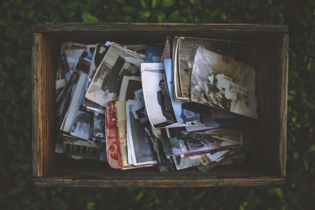 Caixa de madeira cheia de fotos antigas, em preto e branco e em cor. As fotos estão desorganizadas, não há pilhas ou blocos.