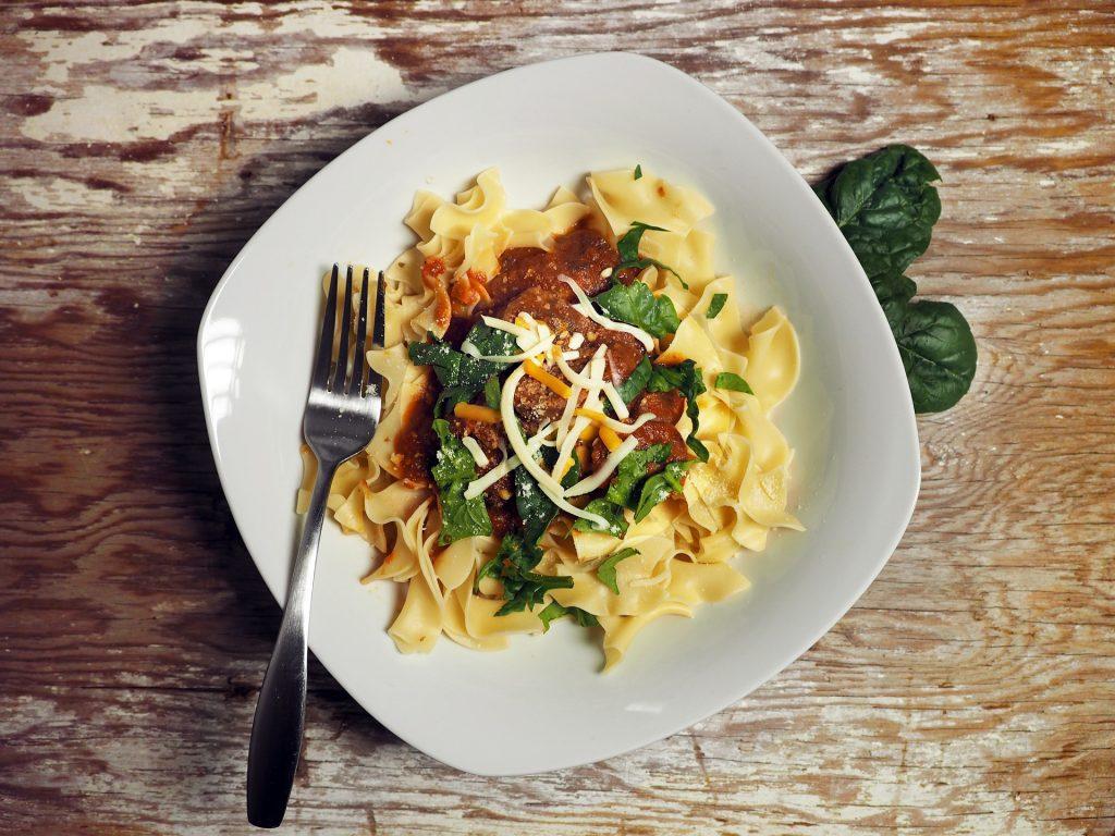 Macarão servido em um prato branco acompanhado de espinafre, molho e queijo.