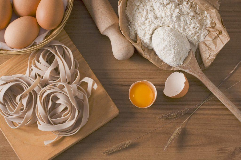 Macarrão tipo Fetuchine. Ao lado uma cesta de ovos vermelhos inteiros. Um rolo de macarrão de madeira, um pacote de farinha de trigo branca, ramos de trigo, um ovo quebrado.