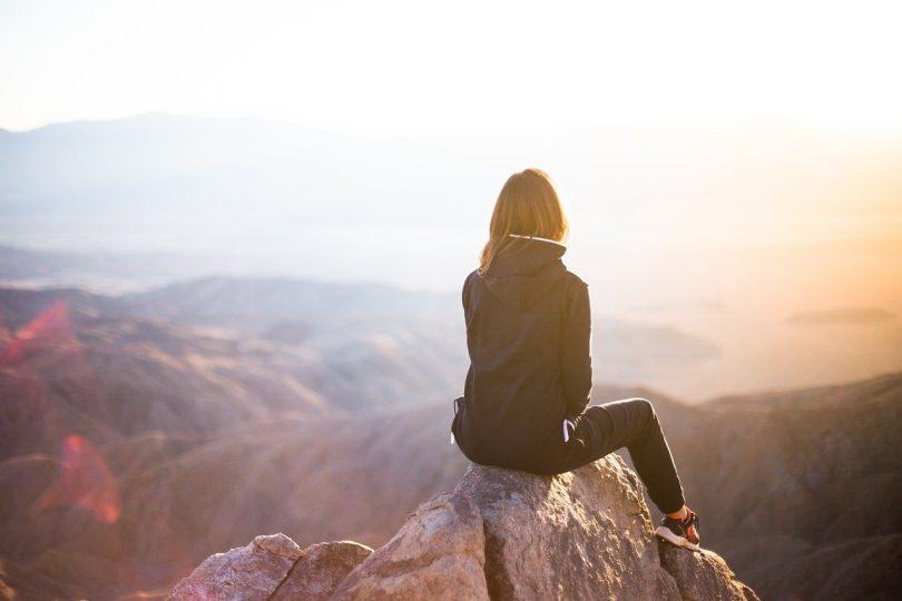 Mulher de costas para a câmera, sentada em uma pedra no topo de uma montanha. Ela veste jaqueta, calça e tênis. Ao fundo, muitas montanhas menores, o mar e o brilho do sol que dificulta a visão do lado direito superior da imagem.