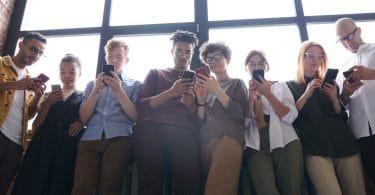 Pessoas encostadas em parede respondendo mensagens em seus celulares