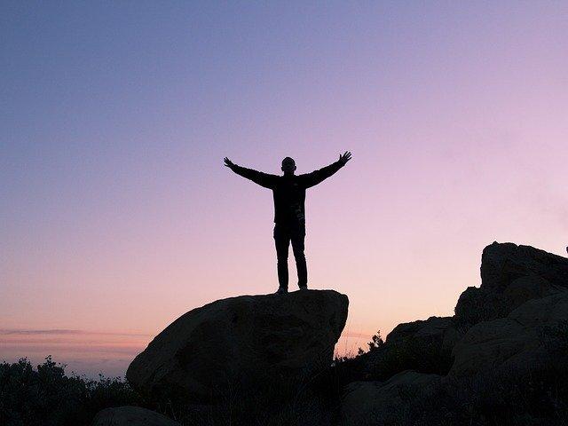 Silhueta de homem com braços abertos em cima de pedra com céu ao fundo ao entardecer