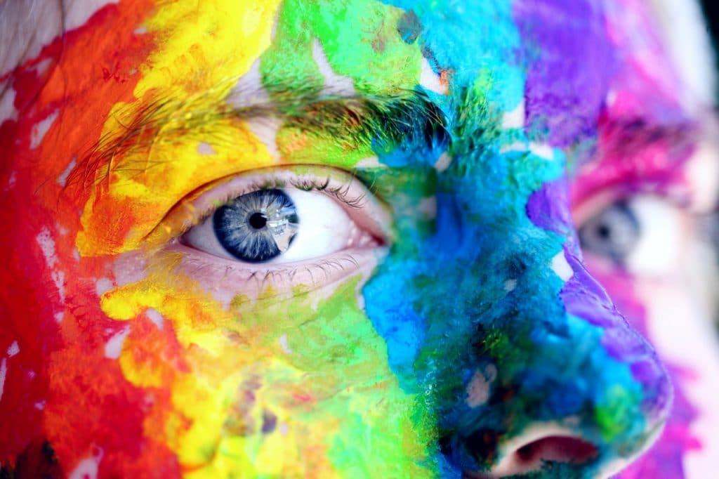 Imagem ampliada de uma pessoa olhando para a câmera com o rosto pintado com tintas de diferentes cores.