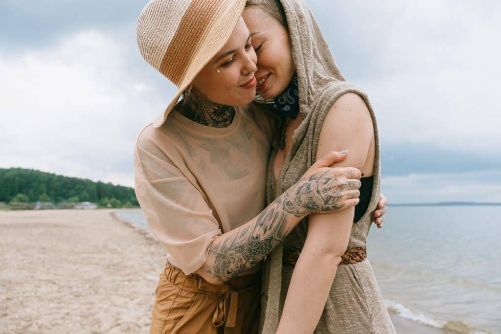 Casal de mulheres se abraçando na praia