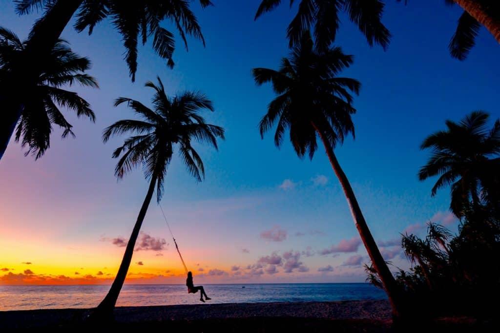 Menina sentada no balanço na praia admirando o entardecer.
