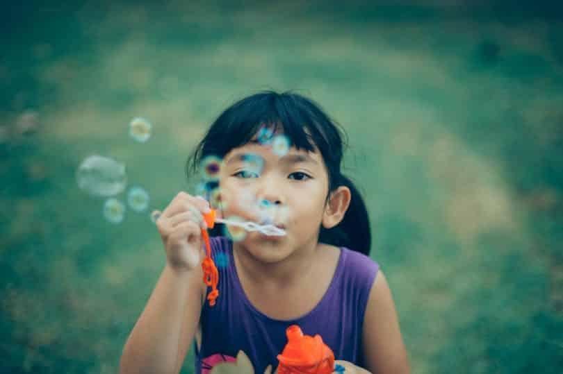 Criança assoprando bolhas de sabão