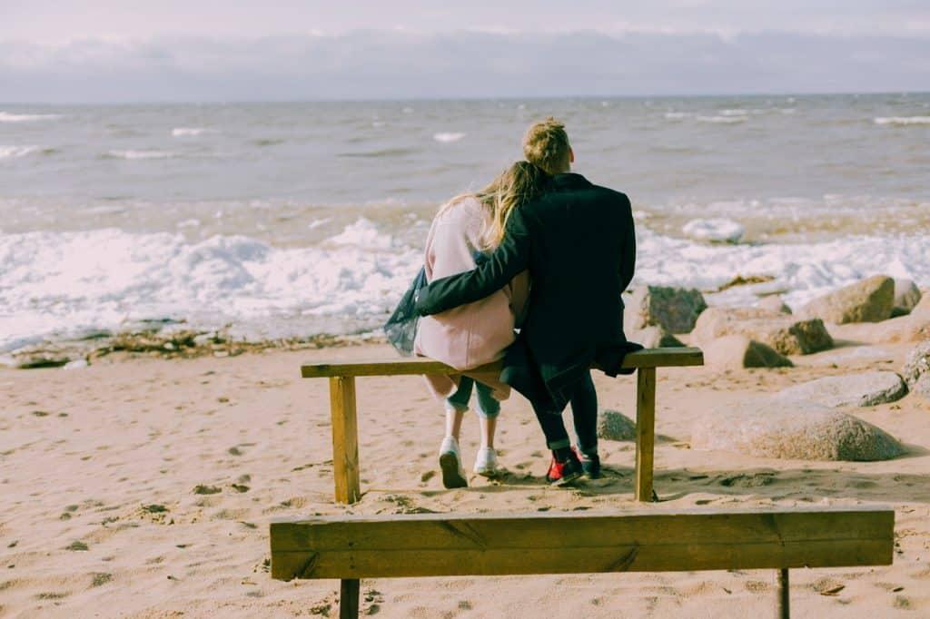 Casal sentado no banquinho de madeira admirando o mar.