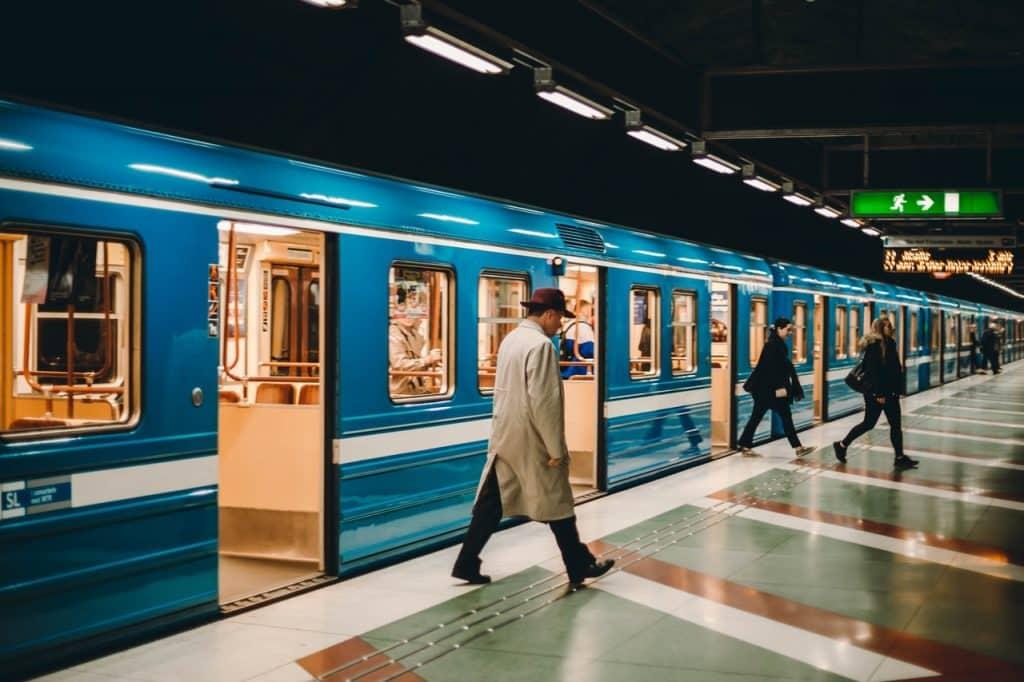 Pessoas saindo de um trem azul que está parado na estação.