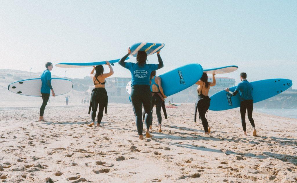 Seis pessoas segurando uma prancha de surfe enquanto caminham na praia.