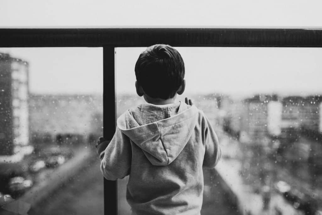 Criança olhando para uma janela com gotas de chuva