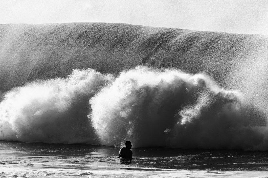 Tsunami se aproximando de um homem.