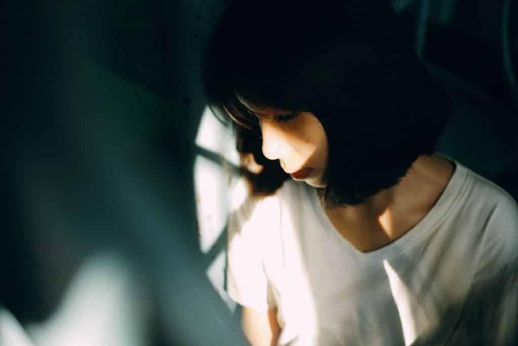 Mulher olhando para baixo com tristeza