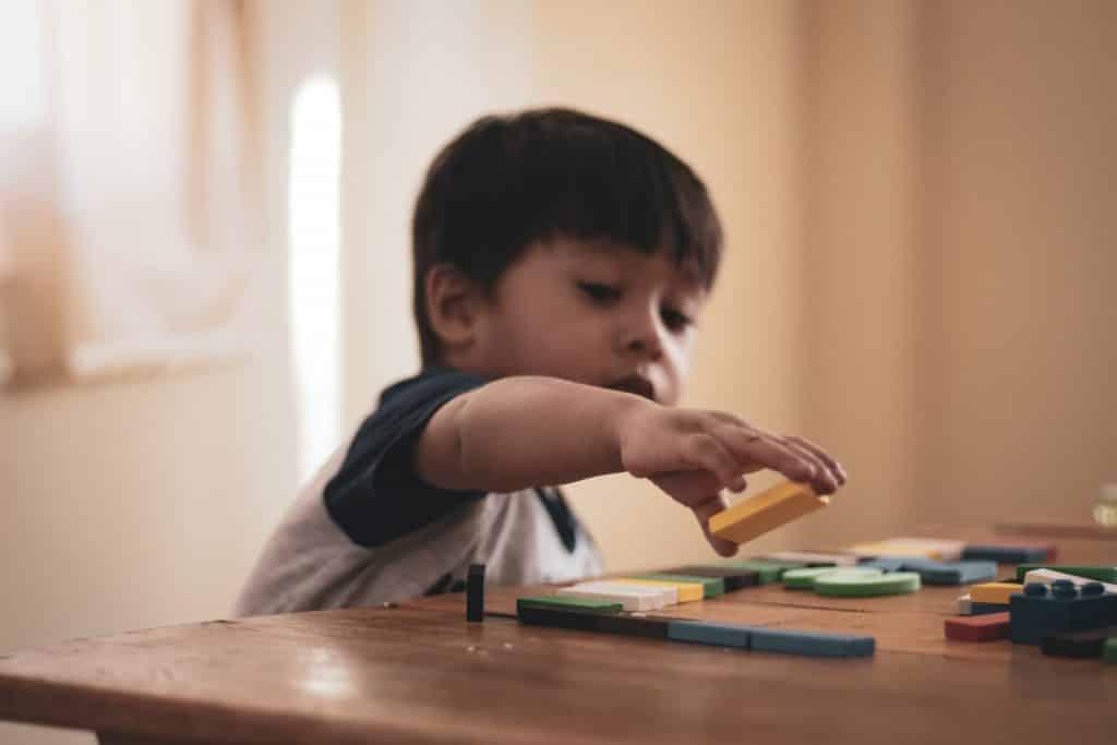 Criança brincando com peças na mesa