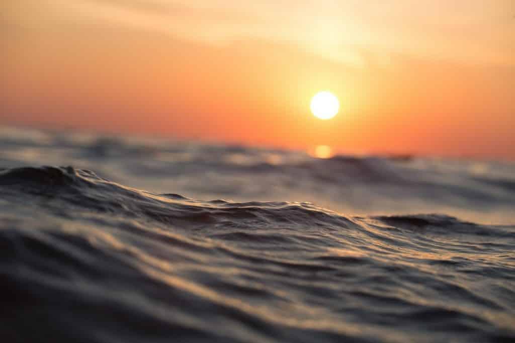 Imagem do mar com o pôr do sol ao fundo.