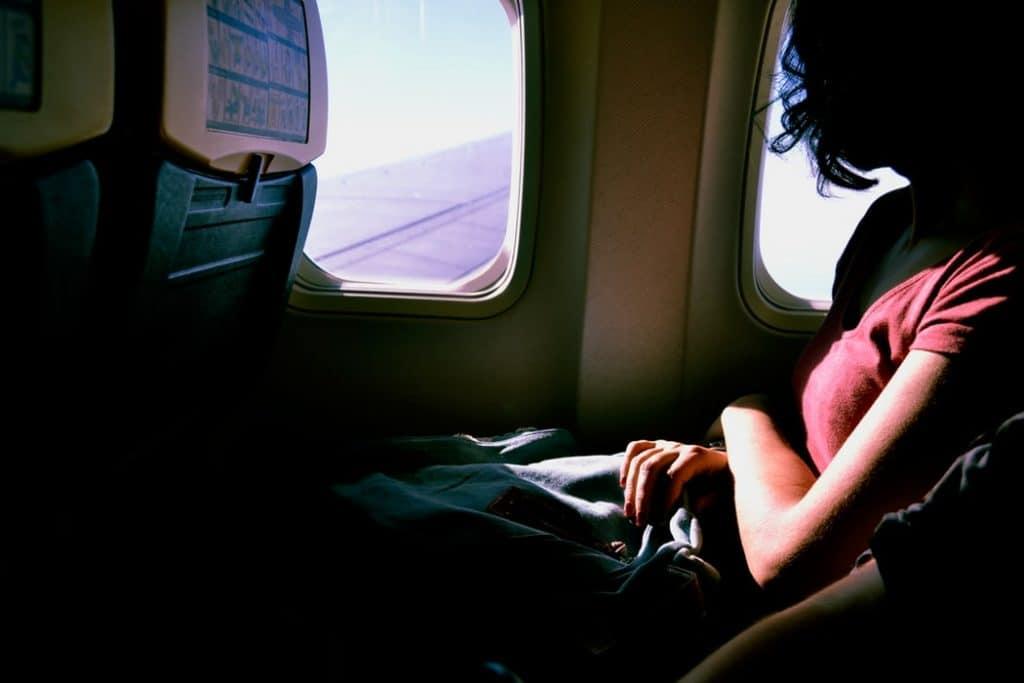 Mulher sentada em poltrona de avião, a mais próxima da janela. Seus braços estão cruzados em cima de suas pernas. Ela olha através da janela e vê a asa do avião, e o céu azul.