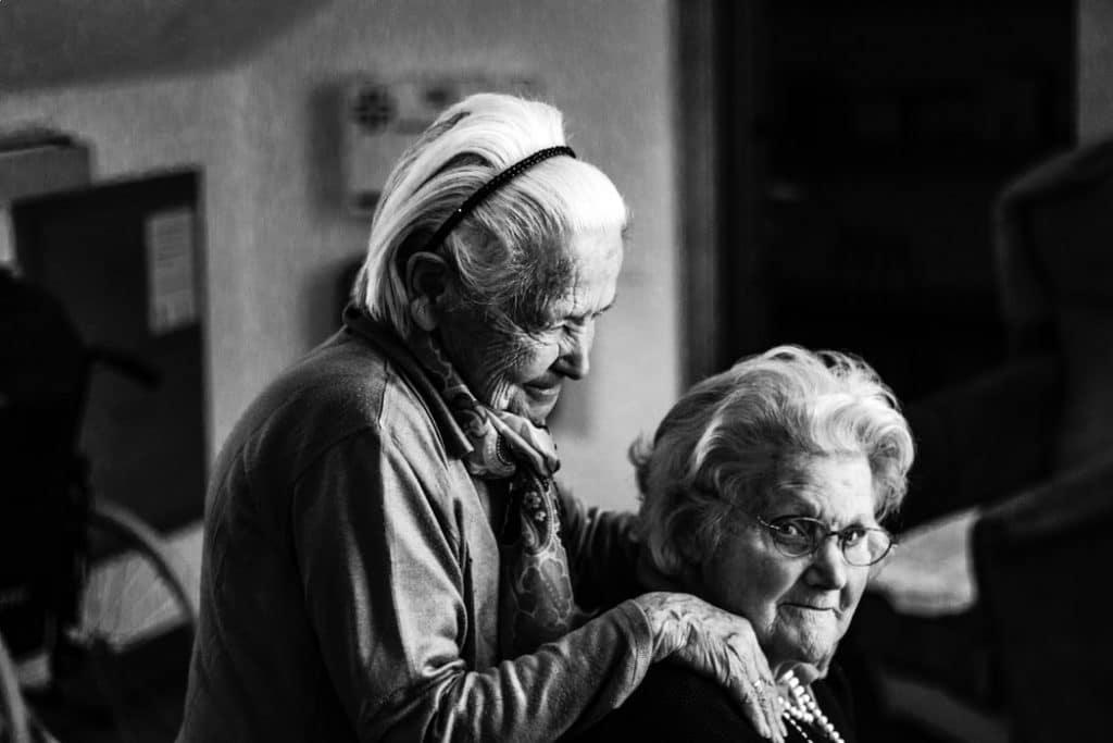 Duas senhoras idosas, uma está sentada e a outra em pé. A que está em pé apoia suas mãos nos ombros da que está sentada. Foto em preto e branco.