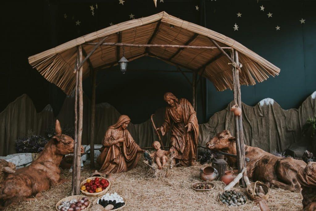 Presépio de madeira em miniatura com Jesus, Maria, José, uma vaca, um cavalo e cestas com frutas e legumes.