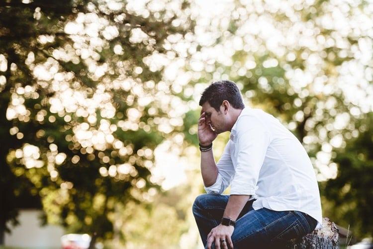Homem sentado em um parque com os olhos fechados e a mão sobre o rosto, em sinal de dor.