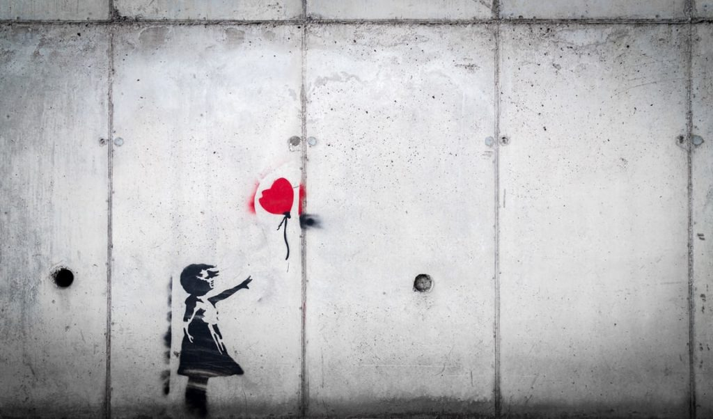 Decalque em parede cinza de menina com o braço esticado em direção a um balão com corta que voa livremente. A única cor do decalque é o balão vermelho, todo o resto está em preto.