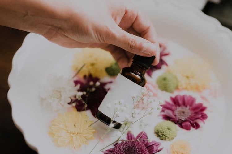 Pessoa segurando um frasco de floral com flores em um prato.