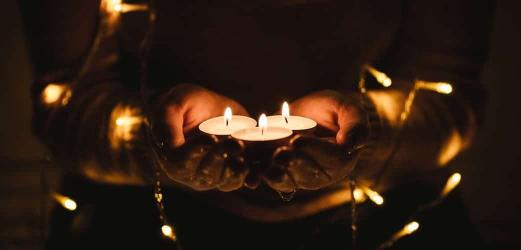 Pessoa segurando velas em ambiente fechado, reodeado por pequenas luzes.