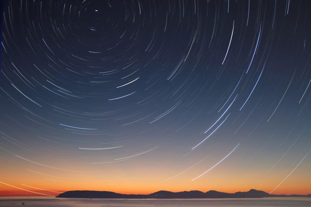 Imagem em time lapse de um céu noturno, rodeado por estrelas, acima de um rio.