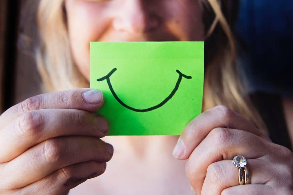 Mulher segurando papel verde com o desenho de um um sorriso na frente do seu rosto, cobrindo sua boca.