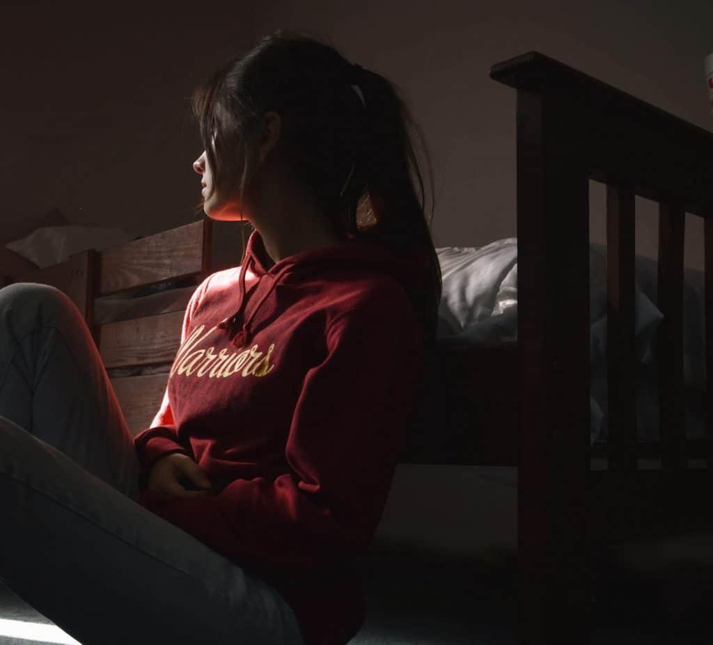 Mulher sentada no chão do quarto encostada na cama