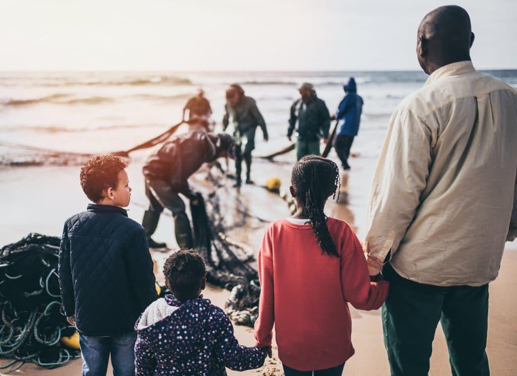 Crianças refugiadas param em frente ao mar, com um adulto e uma equipe de busca.
