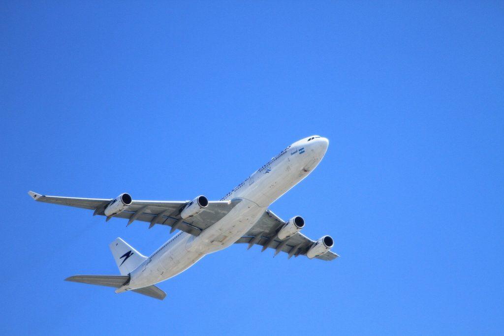Imagem de um avião decolando em um céu azul.