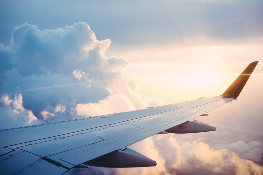 Imagem da asa de um avião no céu azul. Ao fundo nuvens e sol.