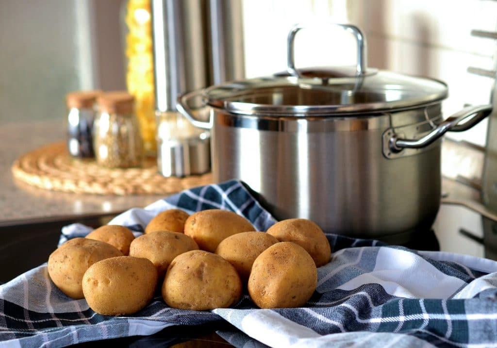 Batatas cruas sobre uma mesa forrada com uma toalha de pano nas cores azul e branco. Ao lado da porção de batatas uma panela grande de inox. Imagem de congerdesign por Pixabay.