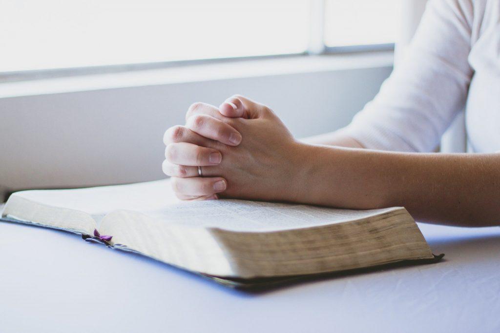 Bíblia grande aberta sobre uma mesa branca. Sobre ela, uma mão feminina em posição de oração.