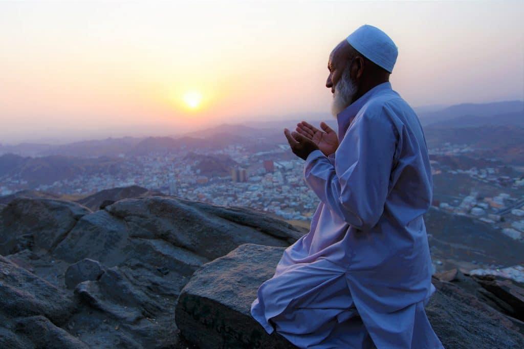 Homem muçulmano em posição de oração. Ao fundo o sol está se pondo. Ele está sobre as pedras.