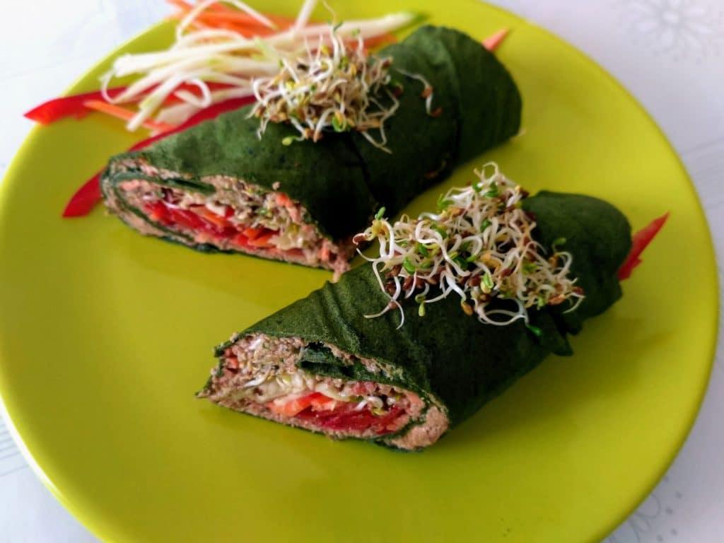 Duas panquecas de espinafre servidas em um prato de porcelana na cor verde claro.