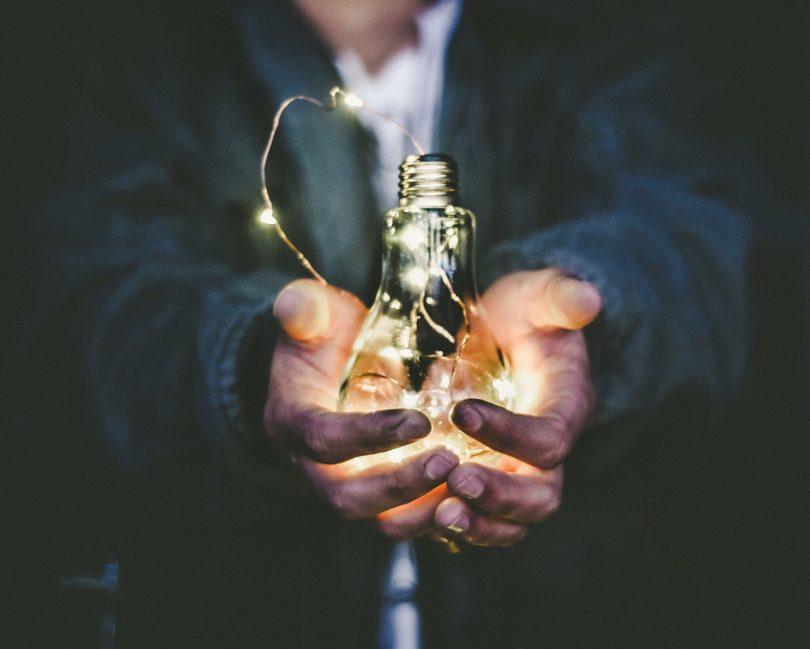 Par de mãos segurando lâmpada.