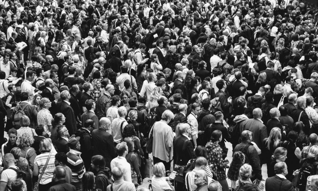 Fotografia de um lugar aberto lotado por uma multidão reunida, de diferentes idades, culturas e etnias.