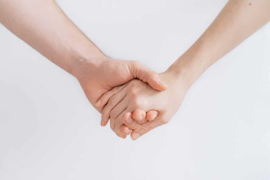 Duas mãos dadas em sinal de ajuda.