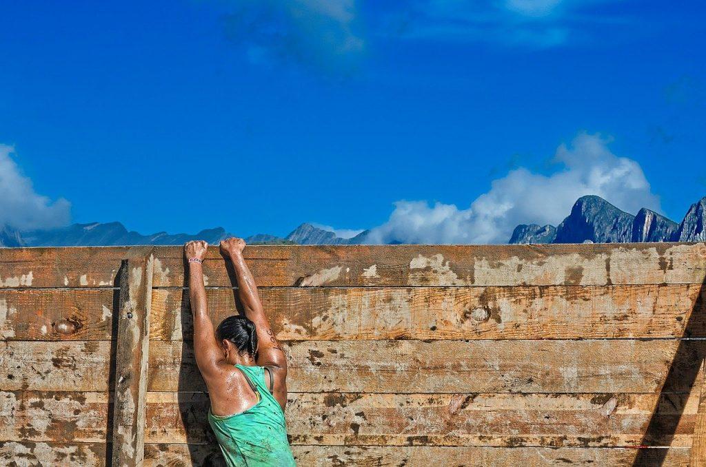 Mulher pendurada pelas duas mãos em muro de madeira. Ela está de costas, suada, com cabelo preso e sua roupa está suja. Ao fundo, o céu está azul.