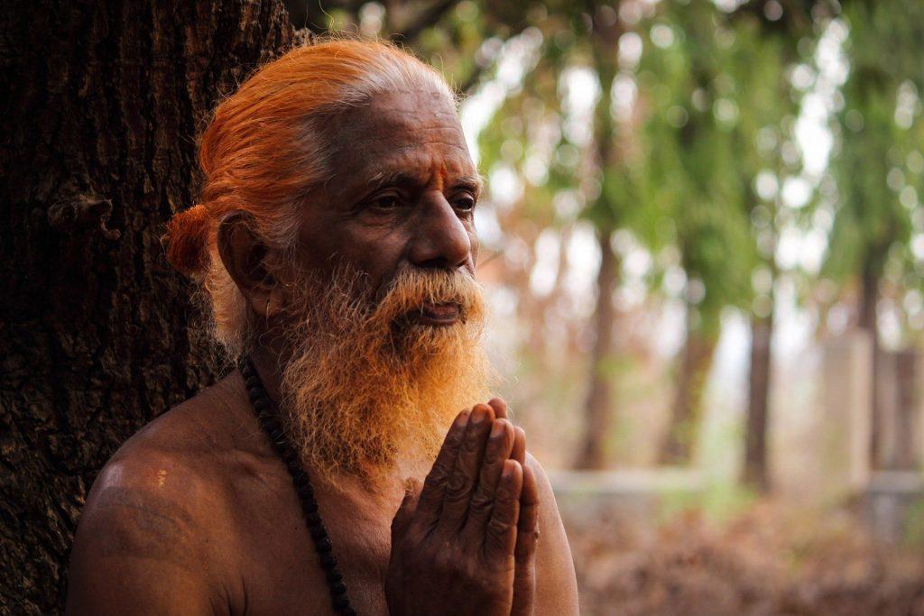 Imagem de um  homem budista com cabelos e barba branco e comprido. Ele está sem camisa e usa um colar de contas.