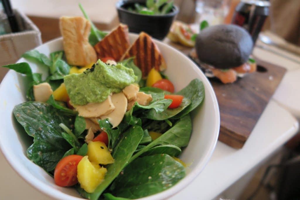 Pasta de espinafre servida com saladas de espinafre, tomates, queijos e torradas.
