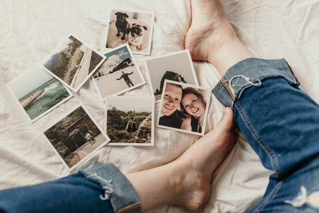Pessoa sentada na cama, de calça jeans, ao lado de várias fotos impressas de memórias da sua vida.