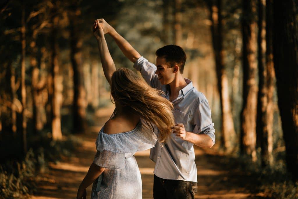 Casal dançando em caminho de terra em floresta
