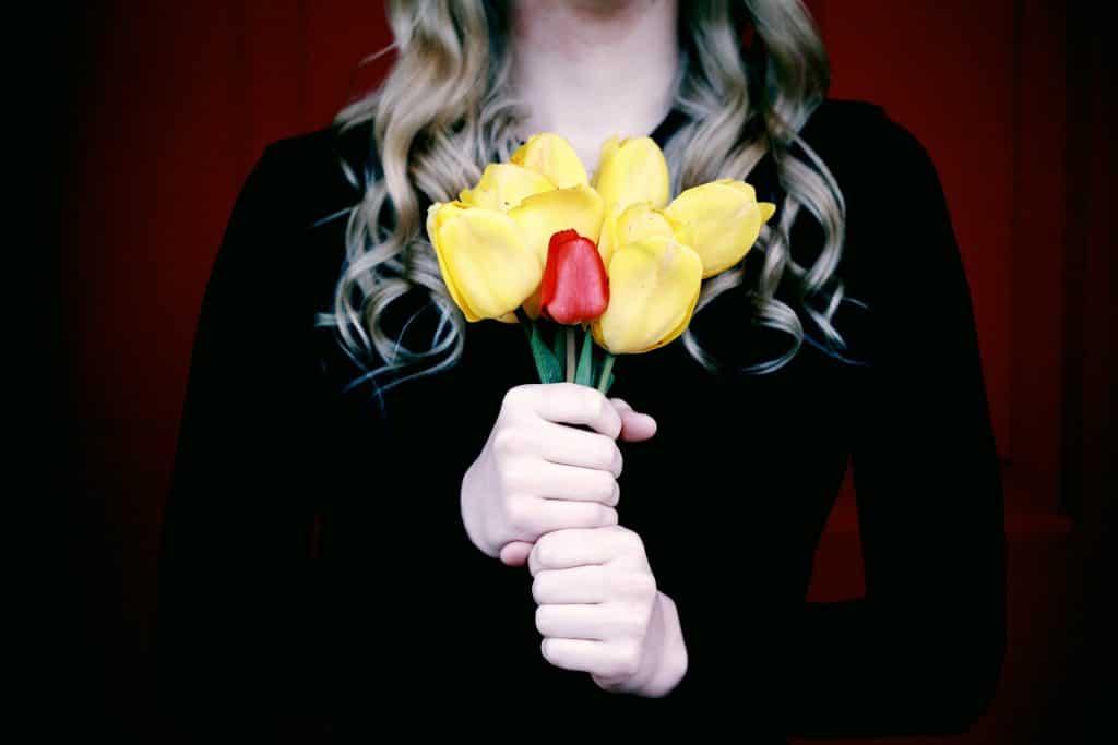 Mulher segurando rosas amarelas e uma vermelha