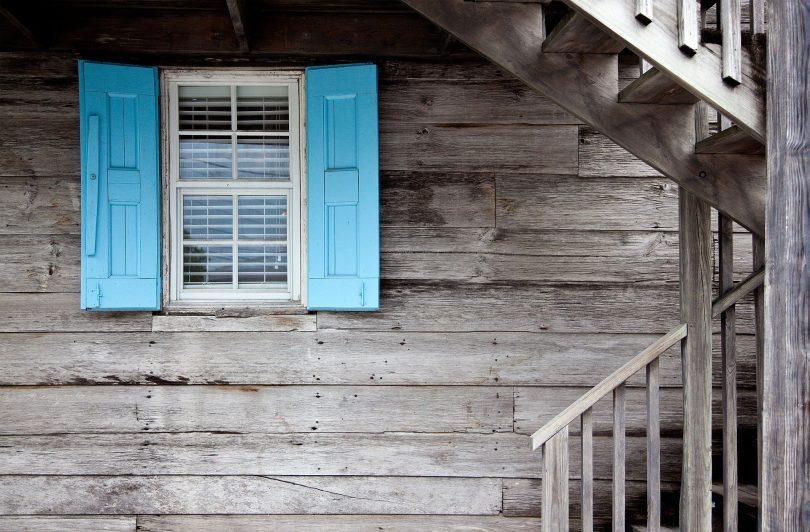 Casa de madeira cinza com janela azul.